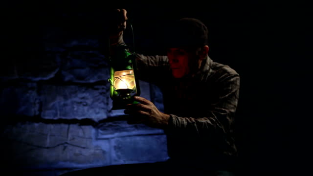 Man lighting an old oil lamp in darkness video