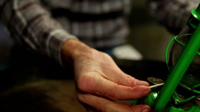 Man lighting an old oil lamp video