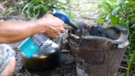 Man lighting charcoal in stove by using flame gas video