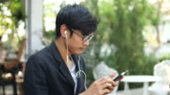 Man listening to music in garden, 4K (UHD) video