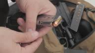 Man Loading Bullets Into a Pistol Magazine video