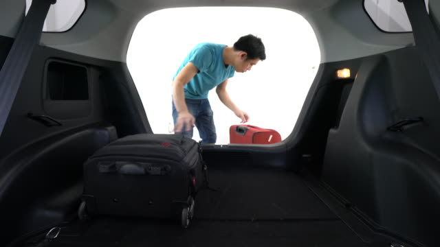 Man Loading Luggage Into Boot of Car video
