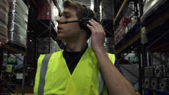Man locating stock in a storage warehouse, shot on R3D video