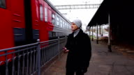 Man look to commuter train rush past local station without stop, turn head video