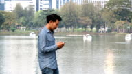 Man looking at mobile phone on the waterfront video