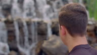 Man looking at waterfall. Closeup of man relaxing at nature video