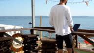 man looking for information in the laptop on the waterfront on sea background video
