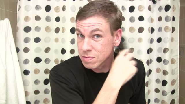 Man looking into camera brushing hair video