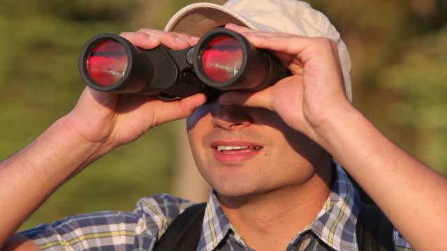 Man looking through binoculars video