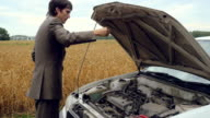 Man looking under hood of old car in countryside. 1920x1080. hd video