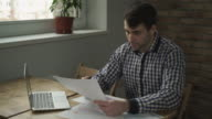A man looks at the table and makes a note in notebook video