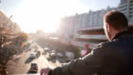 Man looks at traffic in the city in the sunset video
