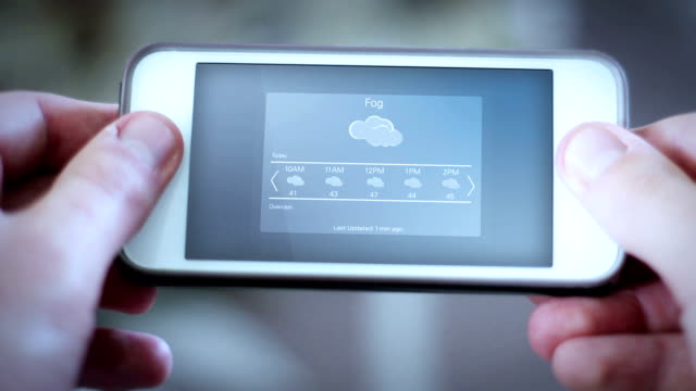 Man looks down at smartphone app with a weather app interface - Foggy day video