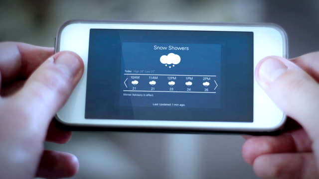 Man looks down at smartphone app with a weather app interface - snow showers video