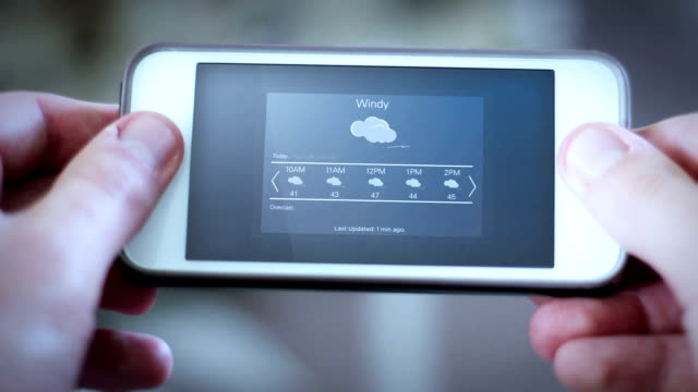 Man looks down at smartphone app with a weather app interface - Windy video