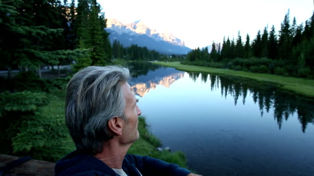 Man looks off down mountain pond at sunrise video