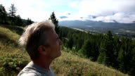 Man looks out across mountains from grassy ridge video