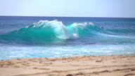 SLOW MOTION: Man lying down on the board while riding big turquoise ocean wave video