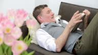 man lying on couch and reading a book video