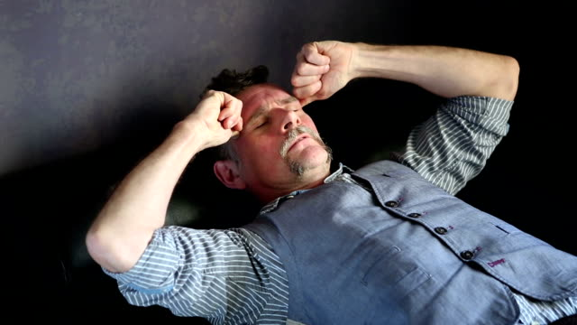 man lying on couch with a headache video