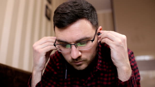Man lying on the couch listening to music and using tablet at home in the living room video