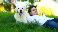 man lying with his dog in the meadow video