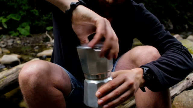 A man makes coffee in a coffee maker in a campsite on the river bank video