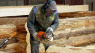 Man makes curly cutting wood Chainsaw. The log will be part of the future of the wooden house. Protective face mask on the face of the builder and a lot of sawdust video