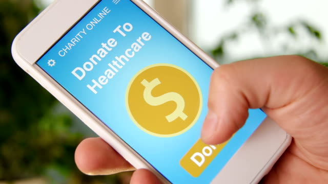 Man making an online donation to healtcare using charity applicaiton on smartphone video