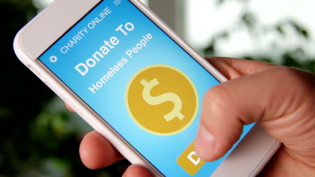 Man making an online donation to homeless people using charity applicaiton on smartphone video
