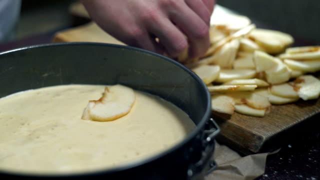 Man making apple pie. Cook puts apple slices into baking pan. Closeup video