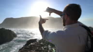 Man making finger frame by the beach at sunset video