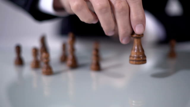 Man making winning queen move in chess game, using successful business strategy video