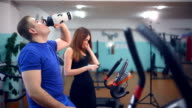 man male athlete drinking water get tired in gym trainers sport video