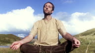 Man meditates by lake timelapse front view video