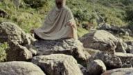 Man meditates on rocks timelapse front view video