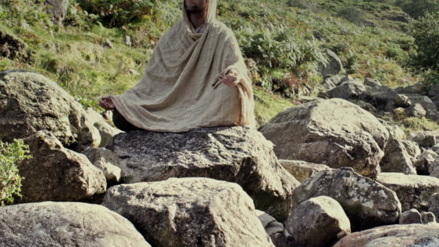 Man meditates on rocks timelapse front view video