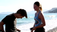 Man meets woman running along surf edge video