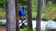 Man mountain bikes through the trees video