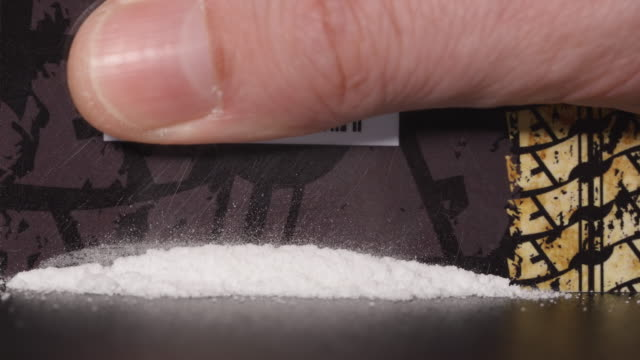 DRUGS: Man moves a lines of heroin by plastic card to the camera video