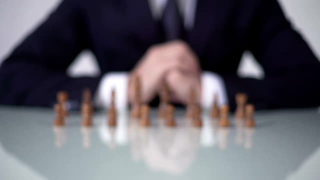 Man moving pawn in chess game, involving voters in unfair political strategy video