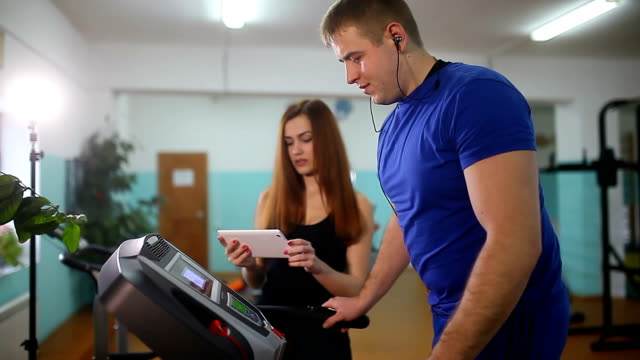 man on a treadmill in the gym Girl on the treadmill trainer, sports a healthy lifestyle video
