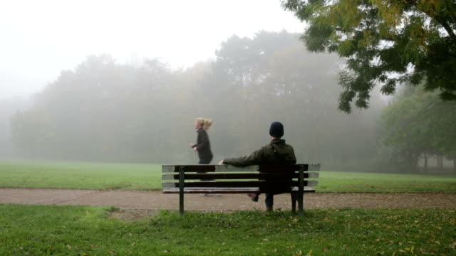 man on bench in park video