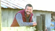 Man on farm outside barn, walks up to wooden fence video