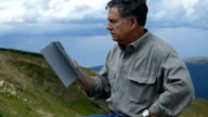 man on mountain looking at a tablet pc video