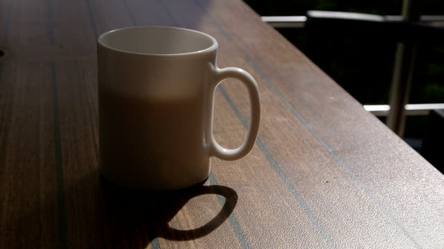 Man on shaded terrace drinking hot coffee in white cup closeup video
