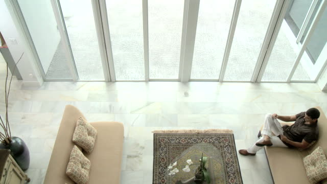 Man on sofa, woman walk past video