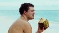 Man on the beach drinking from coconut video