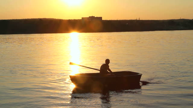 man on the boat at sunset video