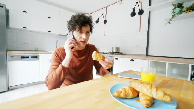 Man on the phone while taking breakfast. video